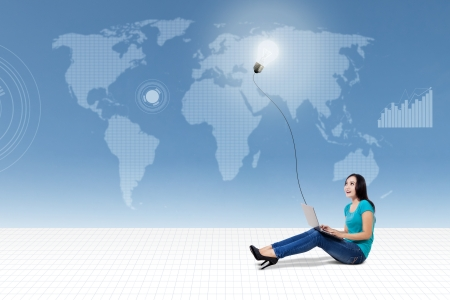 Asian female student using laptop looking at lightbulb on world map background Stock Photo - 22663584
