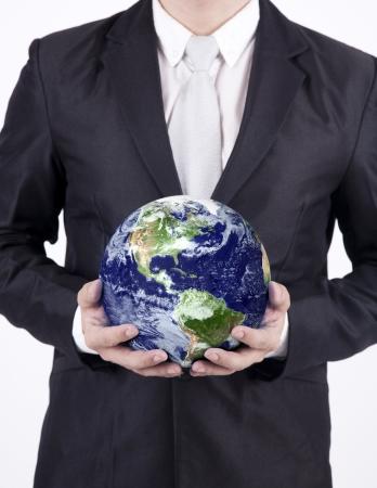 Businessman holding a globe isolated over white background. Confident asian businessman holding the planet earth isolated over white background. Earth image courtesy NASA photo