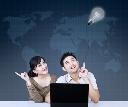 asian couple: Asian couple is looking at lit bulb on blue world map background Stock Photo