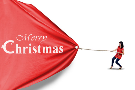 pulling rope: Asian woman is pulling christmas banner isolated on white background