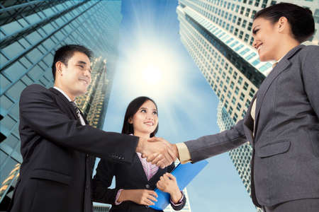 congratulating: Business people congratulating for the new partnership agreement on city background