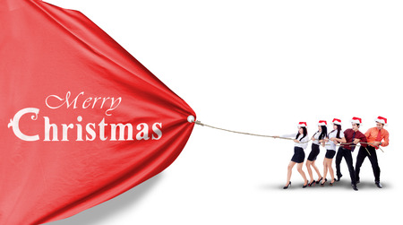 Young asian businesspeople is pulling christmas banner isolated on white background photo