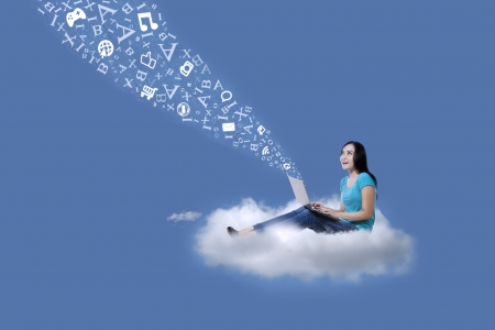 filipino people: Beautiful female student sitting on a cloud under blue sky with laptop and flying letters  Stock Photo
