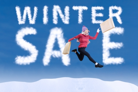 Beautiful woman is jumping and holding shopping bags during winter sale photo