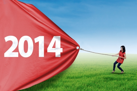 takeover: Asian young woman is pulling new year of 2014 on the meadow Stock Photo