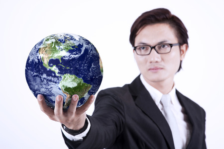 environmental suit: Asian businessman looking smart with glasses holding a globe on white