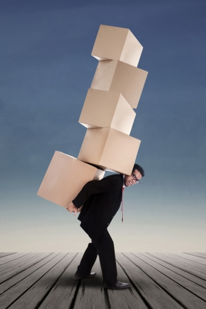 Businessman lifting boxes vertical on the blue sky  photo