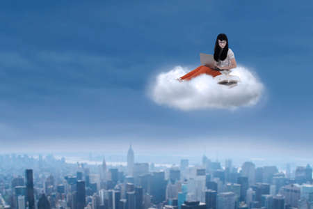 Beautiful asian female student sitting with laptop on a cloud over cityscape photo