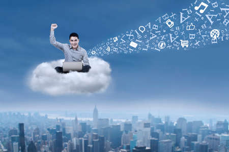Asian male student working with his laptop sitting on a cloud over cityscape photo