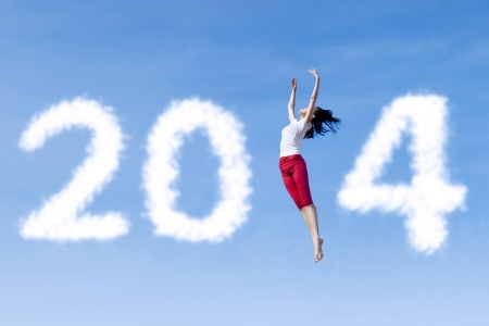 Excited asian woman is dancing with new year 2014 on the sky photo