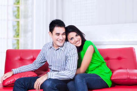 Happy couple relaxing on a red sofa over white  photo