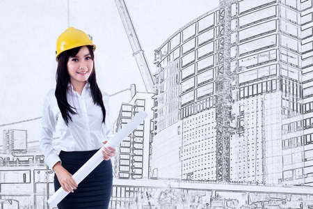 architect drawing: Beautiful young female architect holding blueprint on construction drawing background