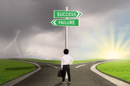 failure sign: Business child is standing on the road with a sign of success or failure  Stock Photo