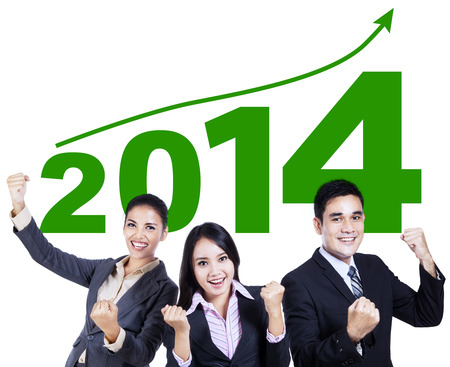successful business: Successful business team celebrating a new year 2014 with arms up