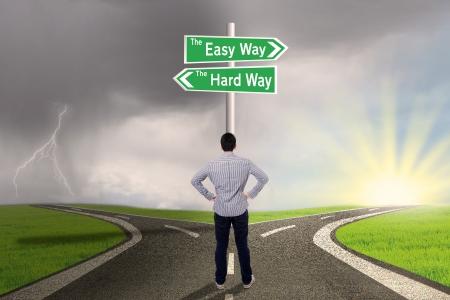 Zakenman staat op de weg met teken van gemakkelijke vs harde manier
