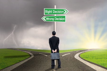 career choices: Businessman looking at sign of right vs wrong decision on highway