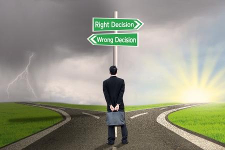 flecha derecha: Empresario busca en el signo de la decisión correcta vs equivocada en la carretera Foto de archivo