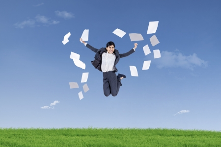 throw paper: Asian businesswoman jumping and throwing papers into air in the green field