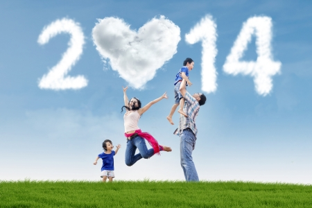 Happy family having fun in the park with heart shaped cloud of new year 2014 photo