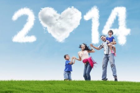 Happy family having fun in the park with heart shaped cloud of new year 2014 Stock Photo - 22961043