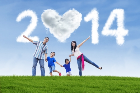 Happy family having fun in the park with heart shaped cloud of new year 2014 Stock Photo - 22961045