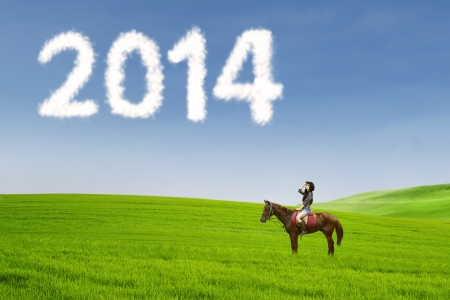 Young woman is riding a horse while looking forward to new year 2014 photo