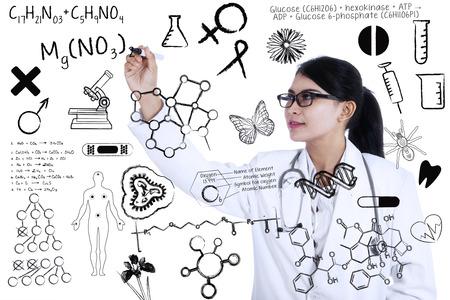 estudiantes medicina: Científico asiático joven escribe la fórmula en la pizarra