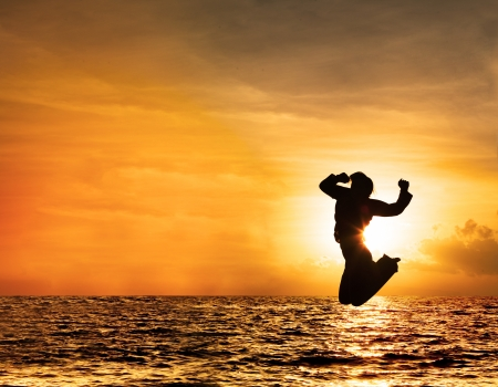 Silhouette of a beautiful jumping woman against orange sky at sunset photo