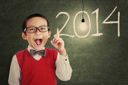 Asian genius student with light bulb and number of new year 2014 shot in a classroom photo