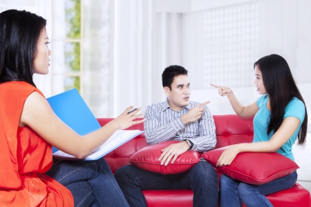couple arguing: Couple arguing during therapy session with psychologist Stock Photo