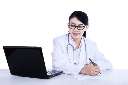 medical notes: Attractive female doctor is writing prescription on white background