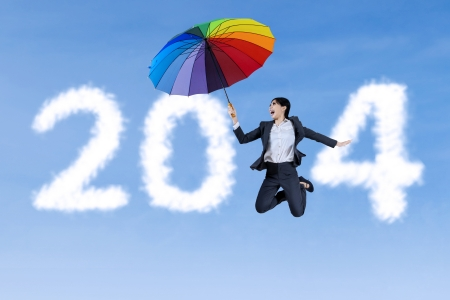 Happy businesswoman holding a colorful umbrella and jumping on new year 2014 cloud photo