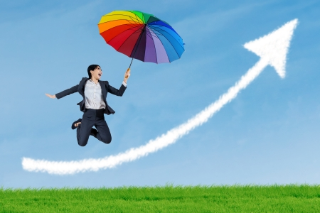 flying woman: Businesswoman jumping to blue sky in grassland with rainbow umbrella