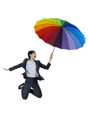 Businesswoman jumping with colorful umbrella isolated on white background photo