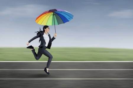 Beautiful businesswoman running under an umbrella on the running track photo
