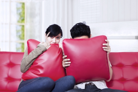 Couple scared watching horror movie at home photo