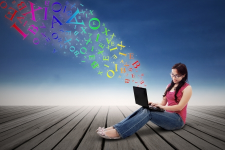 filipino: Asian girl using a laptop computer from which coming out alphabets outdoor