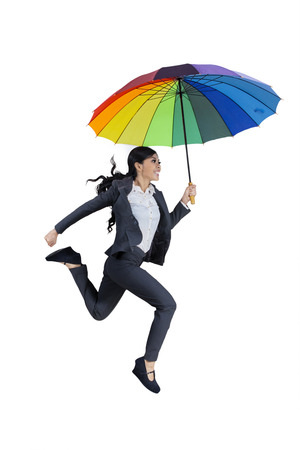 Happy businesswoman jumping with umbrella isolated on white background photo