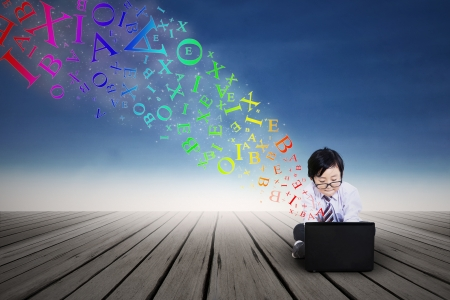 Little boy typing on a laptop with flying alphabet outdoor photo