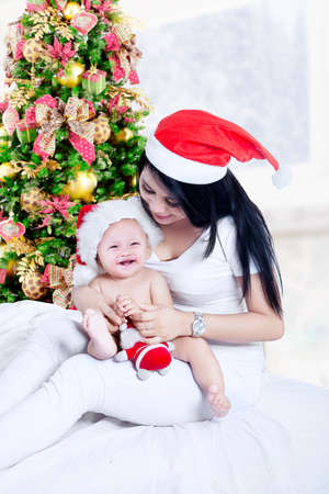 baby near christmas tree: Happy mother playing with lovely baby near Christmas tree