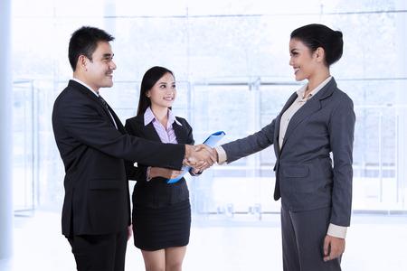 현대 사무실에서 계약을 체결하는 비즈니스 파트너