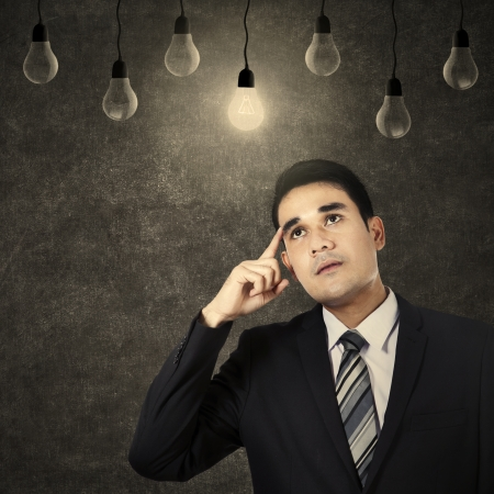 Young businessman having an idea and looking at light bulb photo
