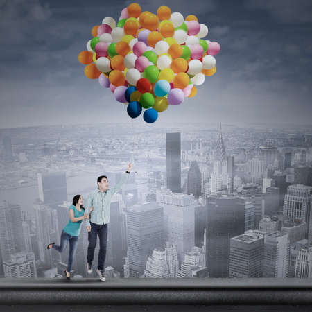 Asian young couple flying with colorful balloons over the cityscape photo