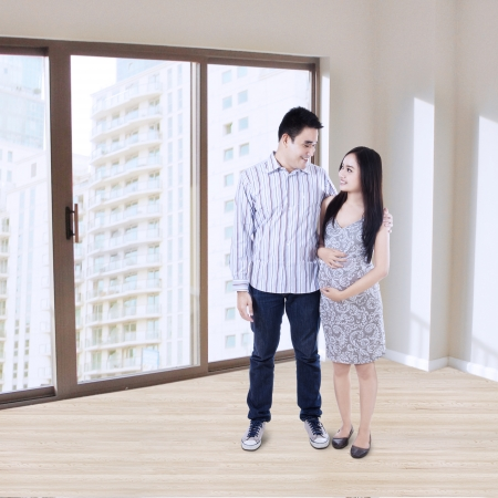 Happy young pregnant couple standing at new apartment photo