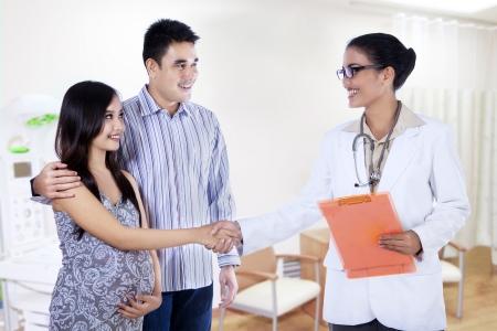 病院の女性医師で、妊娠中の女性の手を振る