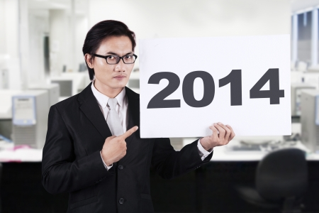 Asian businessman pointing a 2014 billboard on office photo