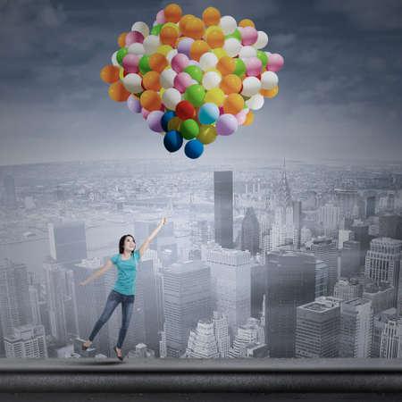 donna volante: Giovane donna asiatica volare con palloncini colorati sul paesaggio urbano