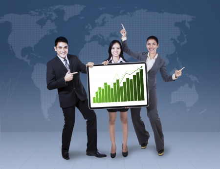 Group of happy business colleagues holding growth graph on world map  photo