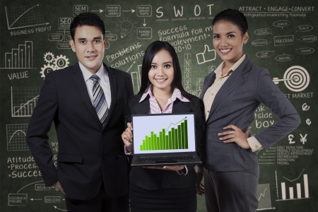 Group of smiling business people holding a board with growth graph photo