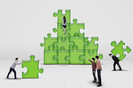 Business team work building a puzzle isolated on white  photo